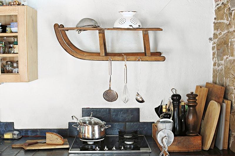 Küchenutensilien hängen an altem Holzschlitten an der Wand in einer Küch